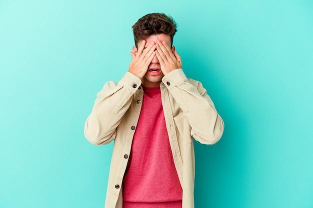 Jeune homme de race blanche isolé sur fond bleu peur couvrant les yeux avec les mains.