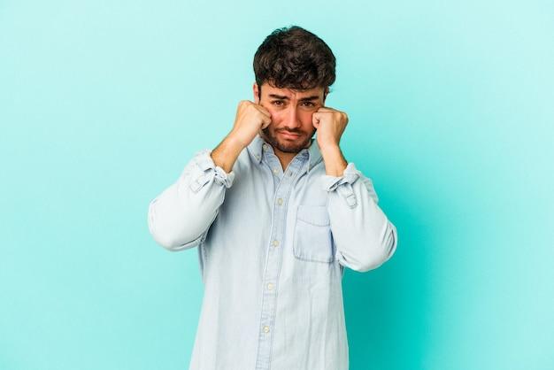 Jeune homme de race blanche isolé sur fond bleu pleurnichant et pleurant de manière inconsolable.