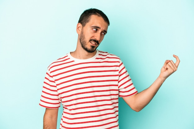 Jeune homme de race blanche isolé sur fond bleu pointant du doigt vers vous comme s'il vous invitait à vous rapprocher.