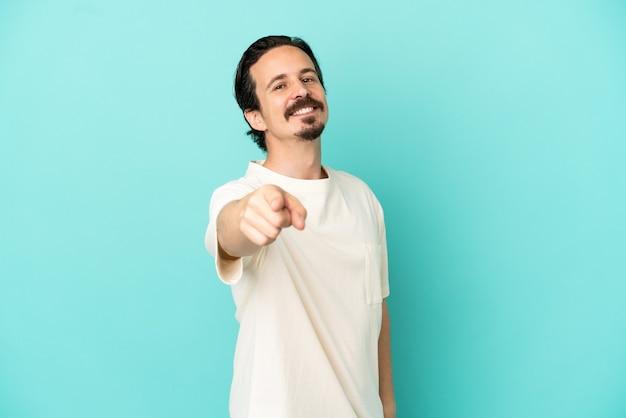 Jeune homme de race blanche isolé sur fond bleu pointant vers l'avant avec une expression heureuse