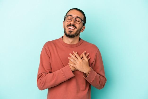 Jeune homme de race blanche isolé sur fond bleu en riant en gardant les mains sur le cœur, concept de bonheur.