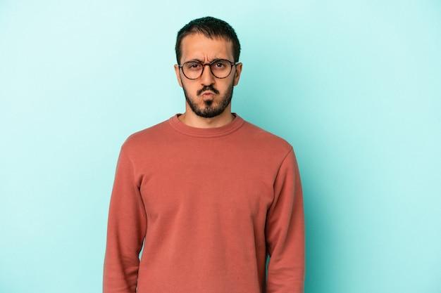 Jeune homme de race blanche isolé sur fond bleu souffle les joues, a une expression fatiguée. concept d'expression faciale.