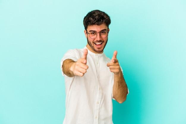 Jeune homme de race blanche isolé sur fond bleu sourires joyeux pointant vers l'avant.