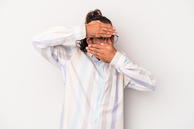 Jeune homme de race blanche isolé sur fond gris clignote à l'appareil photo à travers les doigts, embarrassé couvrant le visage.