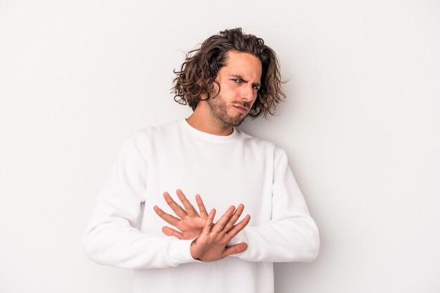 Jeune homme de race blanche isolé sur fond gris faisant un geste de déni