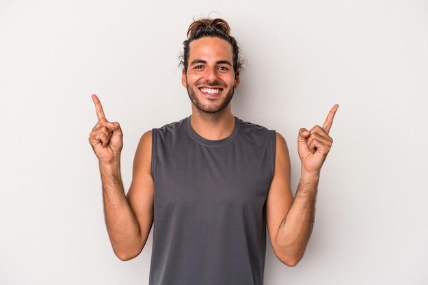 Jeune homme de race blanche isolé sur fond gris indique avec les deux doigts antérieurs montrant un espace vide.