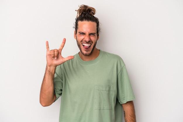 Jeune homme de race blanche isolé sur fond gris montrant un geste de cornes comme concept de révolution.
