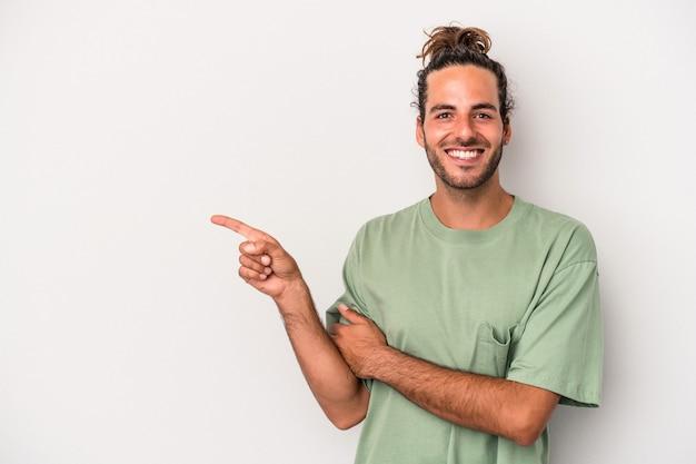 Jeune homme de race blanche isolé sur fond gris souriant joyeusement pointant avec l'index loin.