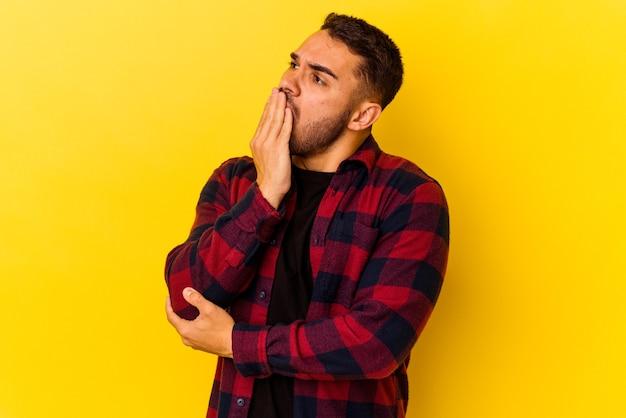 Jeune homme de race blanche isolé sur fond jaune bâillant montrant un geste fatigué couvrant la bouche avec la main.