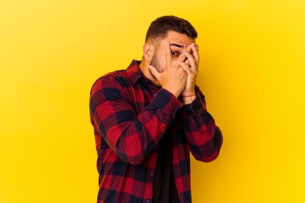 Jeune homme de race blanche isolé sur fond jaune clignote à travers les doigts effrayés et nerveux.