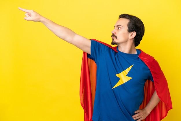 Jeune homme de race blanche isolé sur fond jaune en costume de super-héros avec un geste fier