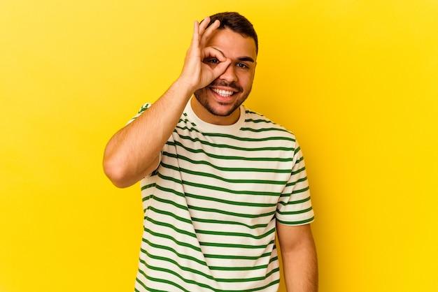 Jeune homme de race blanche isolé sur fond jaune excité en gardant un geste ok sur les yeux.