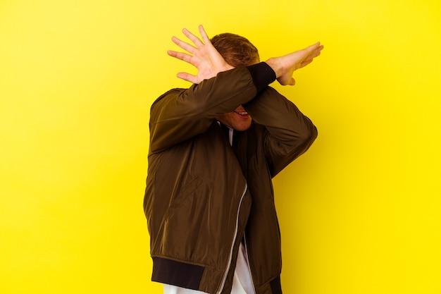 Jeune homme de race blanche isolé sur fond jaune en gardant les deux bras croisés, concept de déni.
