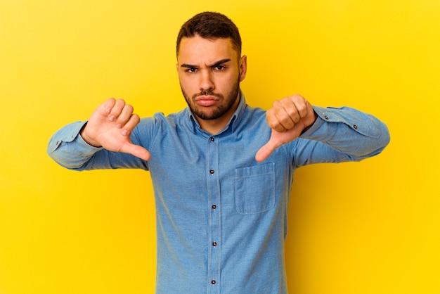 Jeune homme de race blanche isolé sur fond jaune montrant un geste d'aversion, les pouces vers le bas. notion de désaccord.