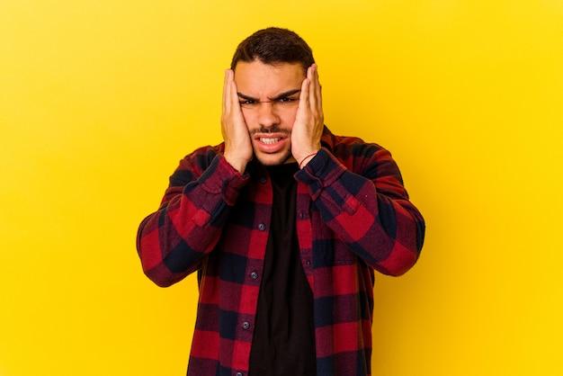 Jeune homme de race blanche isolé sur fond jaune pleurnichant et pleurant de manière inconsolable.