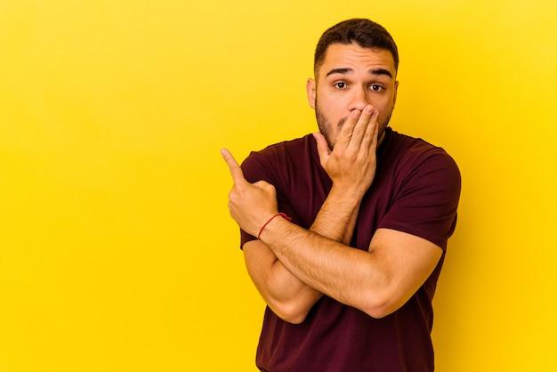 Jeune homme de race blanche isolé sur fond jaune pointant vers le côté