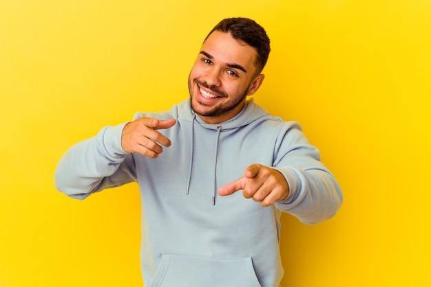 Jeune homme de race blanche isolé sur fond jaune sourires joyeux pointant vers l'avant.