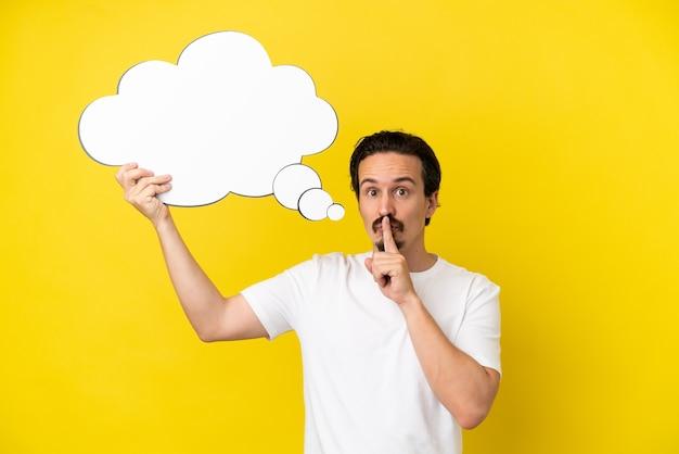 Jeune homme de race blanche isolé sur fond jaune tenant une bulle de pensée et faisant un geste de silence