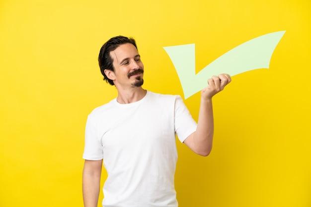Jeune homme de race blanche isolé sur fond jaune tenant une icône de contrôle avec une expression heureuse