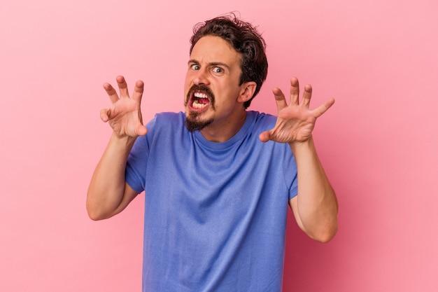 Jeune homme de race blanche isolé sur fond rose bouleversé en criant avec les mains tendues.