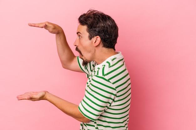 Jeune homme de race blanche isolé sur fond rose choqué et étonné tenant un espace de copie entre les mains.