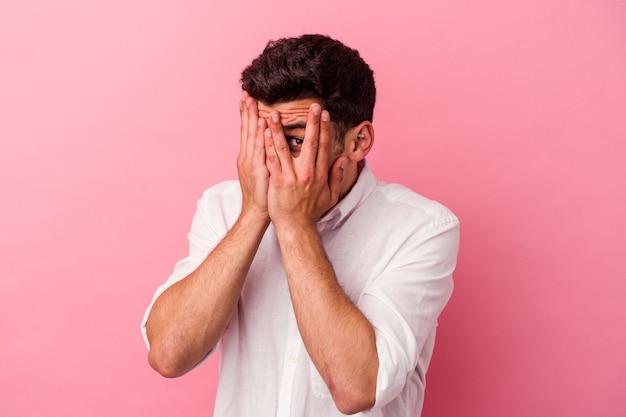 Jeune homme de race blanche isolé sur fond rose clignote à travers les doigts effrayés et nerveux.