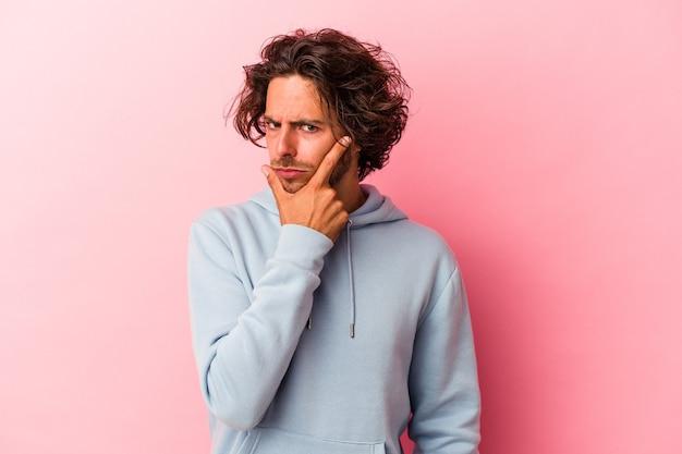 Jeune homme de race blanche isolé sur fond rose contemplant, planifiant une stratégie, réfléchissant à la manière d'une entreprise.