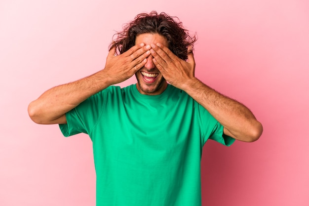 Jeune homme de race blanche isolé sur fond rose couvre les yeux avec les mains, sourit largement en attendant une surprise.