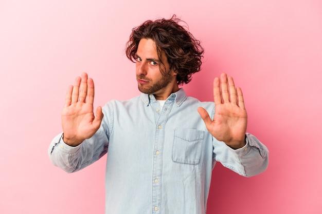 Jeune homme de race blanche isolé sur fond rose debout avec la main tendue montrant un panneau d'arrêt, vous empêchant.