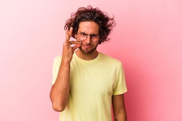 Jeune homme de race blanche isolé sur fond rose avec les doigts sur les lèvres gardant un secret.