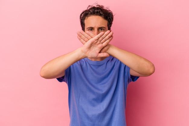 Jeune homme de race blanche isolé sur fond rose faisant un geste de déni