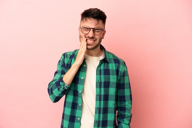 Jeune homme de race blanche isolé sur fond rose avec mal de dents