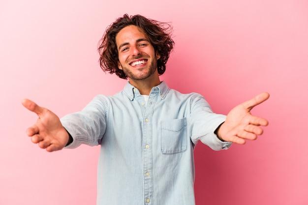 Jeune homme de race blanche isolé sur fond rose montrant une expression de bienvenue.