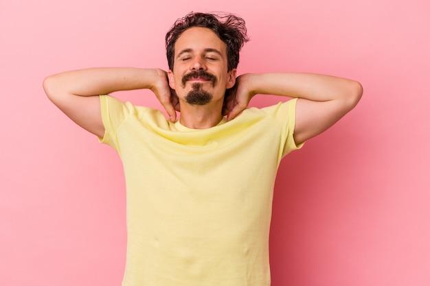 Jeune homme de race blanche isolé sur fond rose se sentant confiant, les mains derrière la tête.