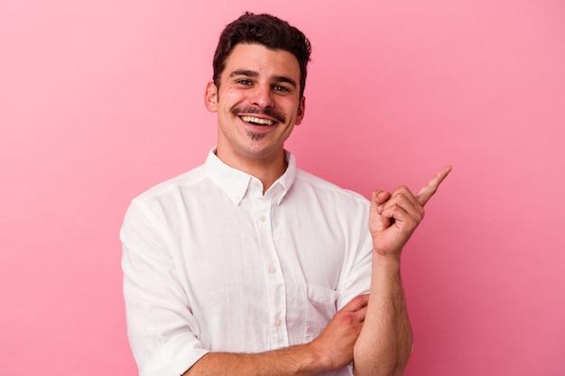 Jeune homme de race blanche isolé sur fond rose souriant joyeusement pointant avec l'index loin.