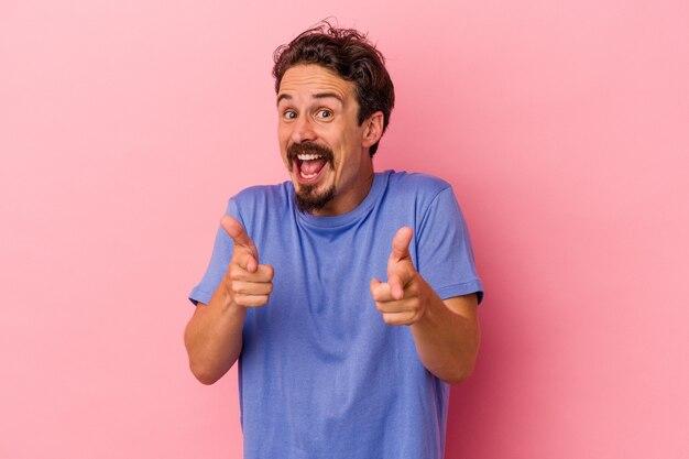 Jeune homme de race blanche isolé sur fond rose sourires joyeux pointant vers l'avant.