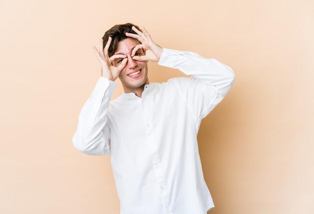 Jeune homme de race blanche isolé sur un mur beige montrant un signe correct sur les yeux