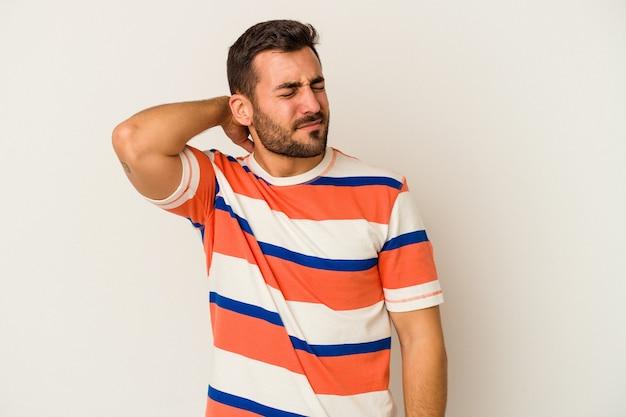 Jeune homme de race blanche isolé sur un mur blanc ayant une douleur au cou due au stress, en massant et en le touchant avec la main