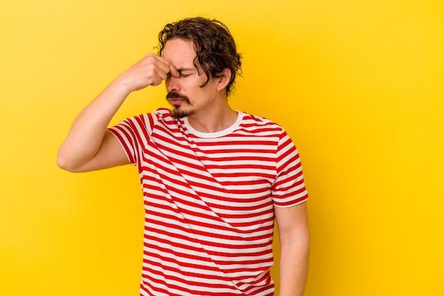 Jeune homme de race blanche isolé sur un mur jaune ayant mal à la tête, touchant l'avant du visage