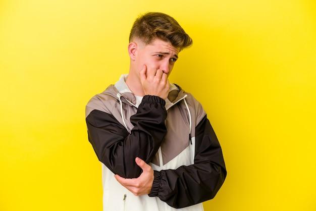 Jeune homme de race blanche isolé sur mur jaune se ronger les ongles, nerveux et très anxieux