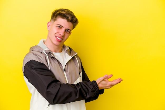 Jeune homme de race blanche isolé sur un mur jaune tenant un espace de copie sur une paume