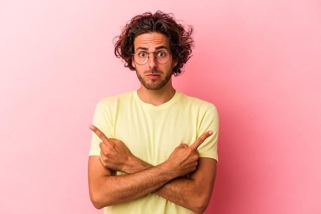 Un jeune homme de race blanche isolé sur des points roses bakcground sur le côté essaie de choisir entre deux options.