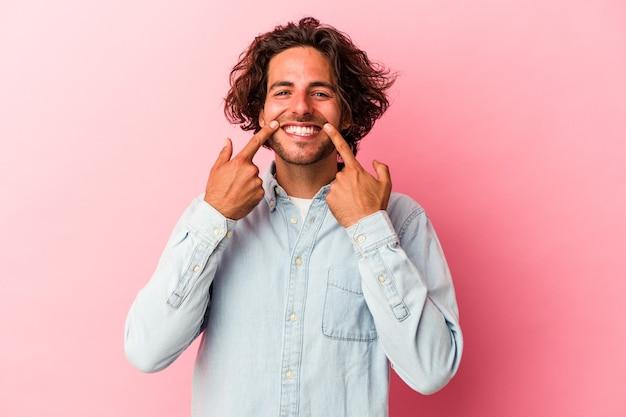 Jeune homme de race blanche isolé sur des sourires de bakcground rose, pointant du doigt la bouche.