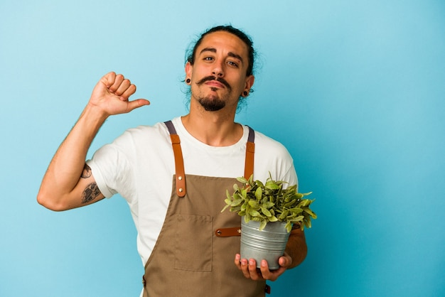 Jeune homme de race blanche jardinier tenant une plante isolée sur fond bleu se sent fier et confiant, exemple à suivre.