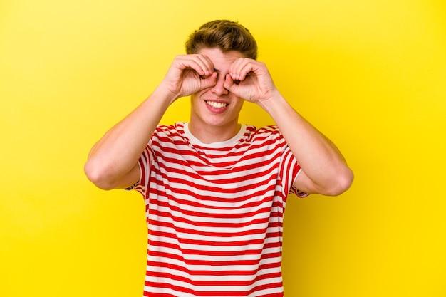 Jeune homme de race blanche sur jaune montrant signe correct sur les yeux