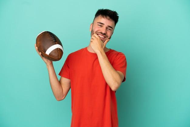 Jeune homme de race blanche jouant au rugby isolé sur fond bleu heureux et souriant