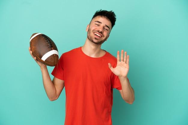 Jeune homme de race blanche jouant au rugby isolé sur fond bleu saluant avec la main avec une expression heureuse