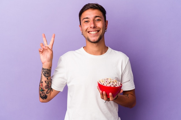 Jeune homme de race blanche mangeant des céréales isolé sur fond violet joyeux et insouciant montrant un symbole de paix avec les doigts.