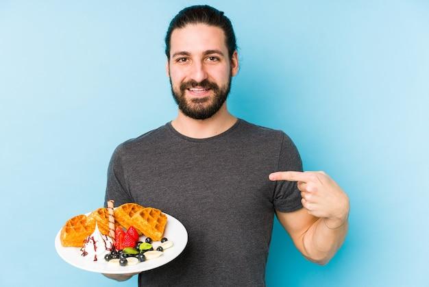 Jeune homme de race blanche mangeant une personne isolée dessert gaufre pointant à la main vers un espace de copie de chemise, fier et confiant