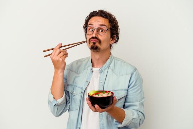 Jeune homme de race blanche de manger un ramen isolé sur fond blanc